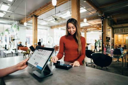 Photo d'une femme qui passe sa carte bleue dans un terminal de paiement digital