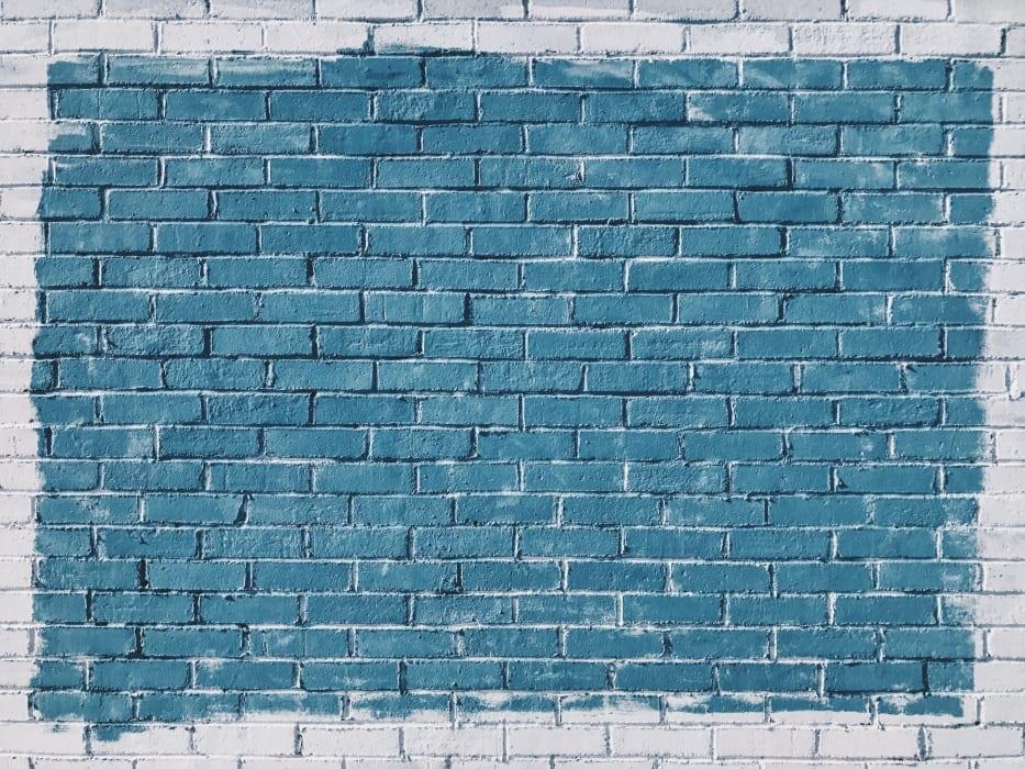 Photo d'un mur en brique blanc avec un grand carré bleu peint sur ce dernier