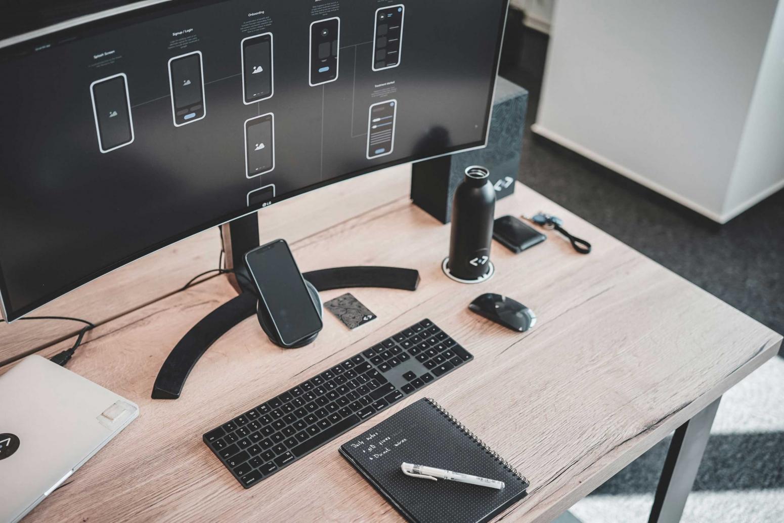 Photo d'un ordinateur posé sur un bureau avec un carnet et un téléphone