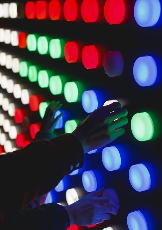 photo d'un mur noir avec des boutons de lumière de lumière bleue, vert et rouge