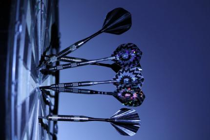Zoom sur une cible avec ses fléchettes, la photo a un filtre de couleur bleu représentant ici la gamification