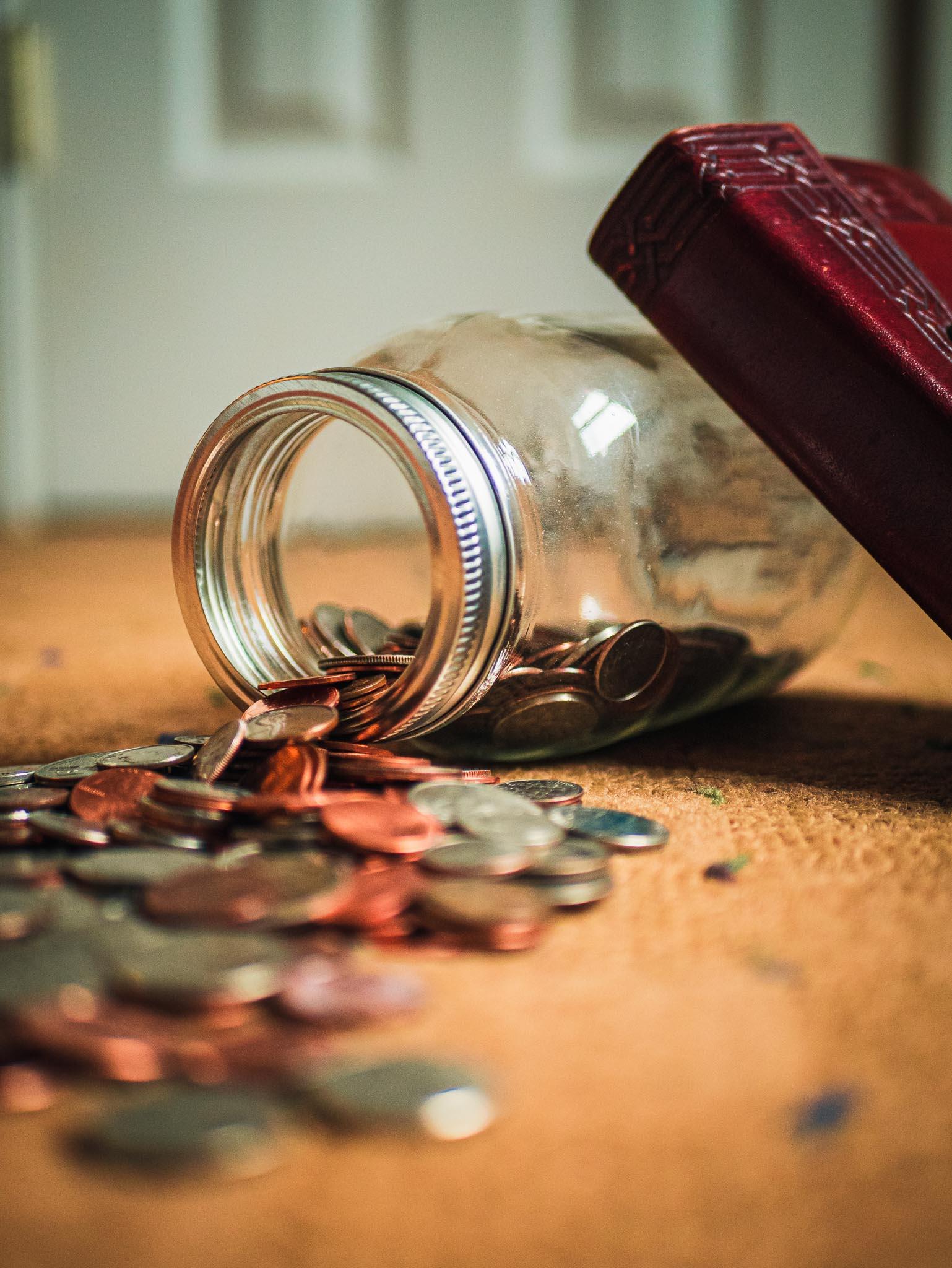 Photo d'un bocal en verre renversé sur une table remplit de pièce et ces dernières tombent sur la table