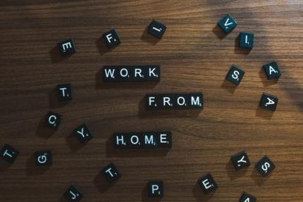 Photo d'un scrabble de couleur noir avec les lettres blanches sur une table en bois on y voit les mots suivants sous forme de Scrabble : work, from, home