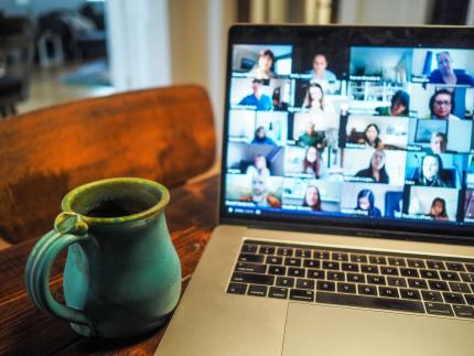 Photo d'un ordinateur on y voit plusieurs personnes qui sont en visio, l'ordinateur est sur un bureau et à sa gauche on y voit une tasse de couleur bleue