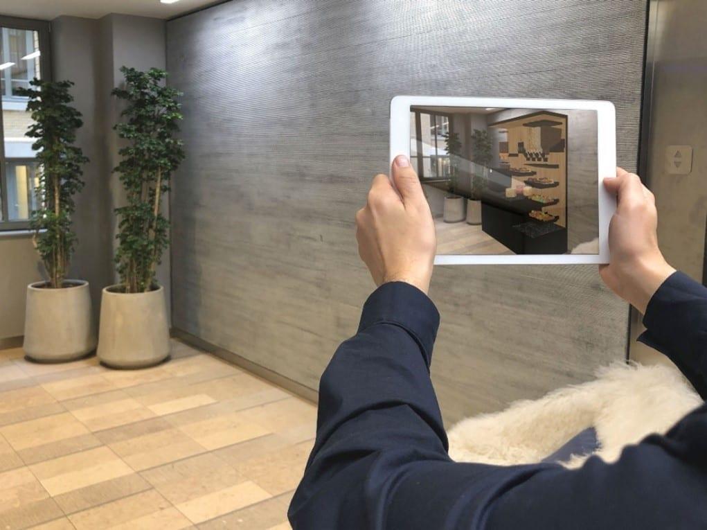 Photo d'une personne qui tient une tablette dans les mains devant une pièce vide. Sur la tablette nous voyons un logiciel qui a créé l'intérieur de la pièce en plan 3D