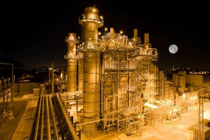 Photo prise de nuit d'une usine complètement éclairée
