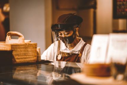 Photo d'une artisane qui produit du café et qui porte une visière de protection, flouté on y voit son comptoir de travail