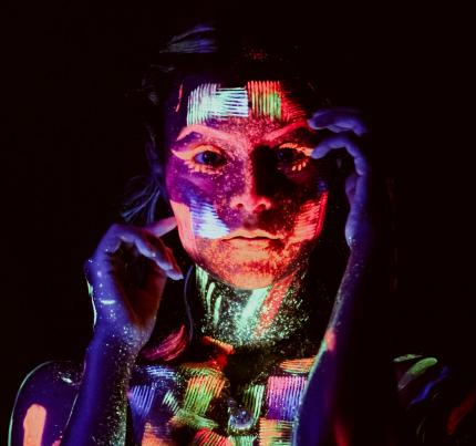 Photo format portrait d'une femme dans le noir avec du maquillage fluorescent
