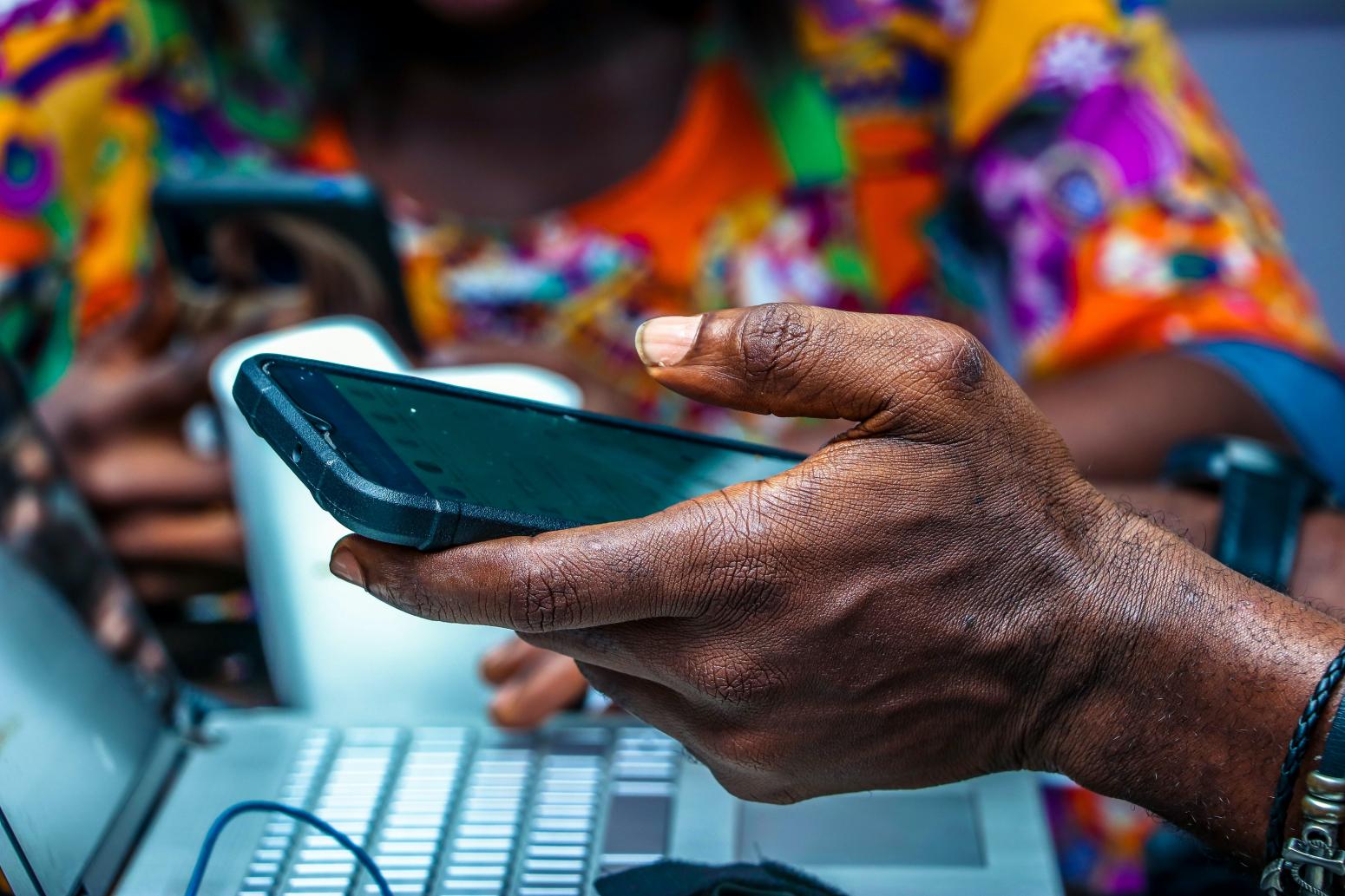 Photo d'une personne au Nigeria tenant un téléphone dans la main et un ordinateur devant elle accompagnée d'une autre personne au second plan